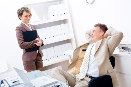 Satisfied businessman sitting by desk at office and smiling to secretary. Stock Photo - 2383419
