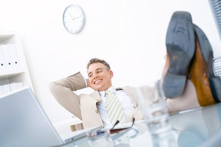 Satisfied businessman sitting by desk at office, feet on table, smiling.