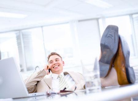Satisfied businessman sitting by desk at office and calling on phone, feet on table, smiling. photo