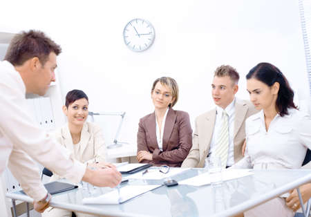 Businessman leaning on desk, explaining to four colleagues sitting in front of. Stock Photo