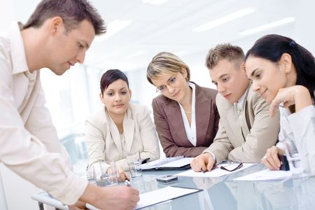 Businessman leaning on desk, explaining to four colleagues sitting. Stock Photo - 2383423