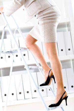Businesswoman climbing on ladder to seek files on shelf.