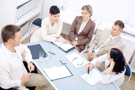 businessmeeting: Five business colleagues sitting around table and having a meeting. Stock Photo