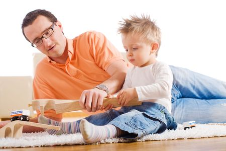 Father and two year old child playing together with wooden toy train. Sitting on floor at home. photo