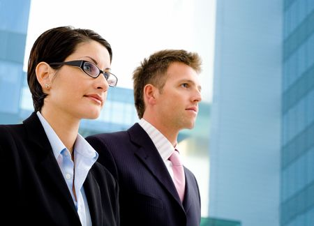 Young business people standing in front of a modern office building. photo