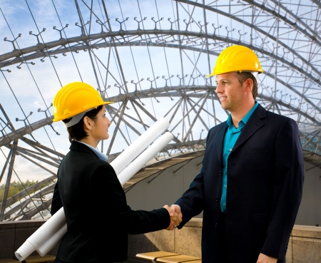 Young architects wearing a protective helmet shaking hands indoor. Stock Photo - 2433883