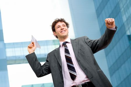 Happy businessman throwing paper airplane. photo