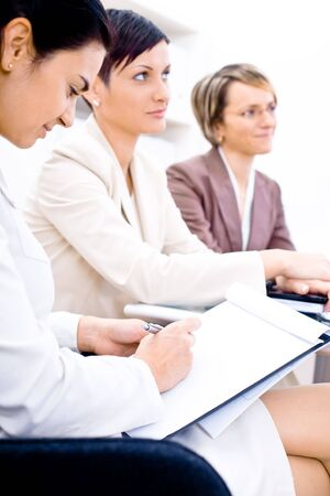 businessmeeting: Three businesswoman attending on business training. Sitting in a row, making notes, smiling. Stock Photo