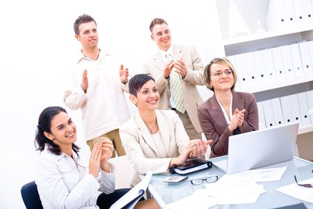 Group of five happy business people smiling and clapping, looking at same direction. photo