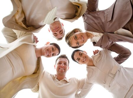 huddle: Small group of business people standing in huddle, smiling, low ange view. Stock Photo
