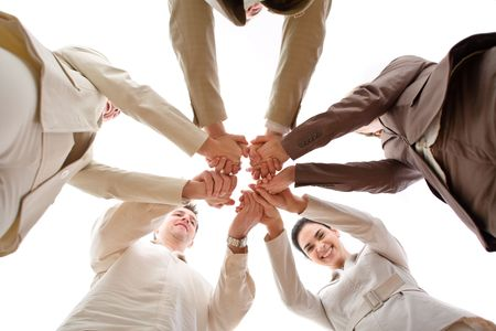 huddle: Five business people forming a circle and holding hands, smiling, low angle view.
