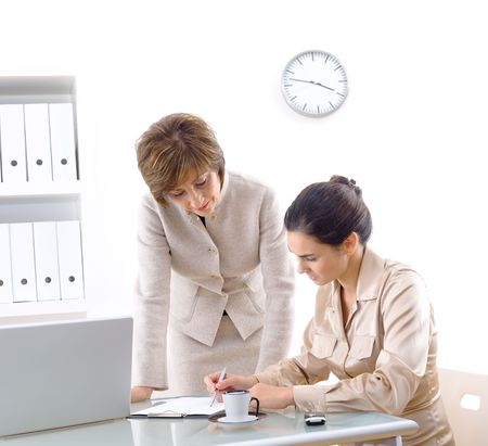 Senior businesswoman teaching younger assiciate in office, smiling. Stock Photo - 2460000