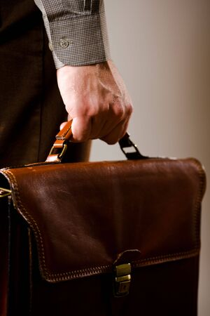 Business man holding elegant brown leather briefcase. photo