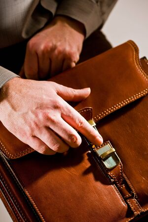 Business man opening elegant brown leather briefcase. photo
