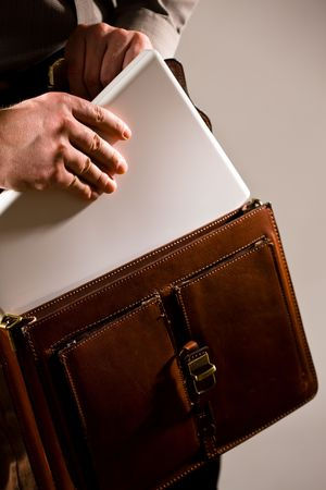 Business man opening elegant brown leather briefcase to take out laptop computer. photo