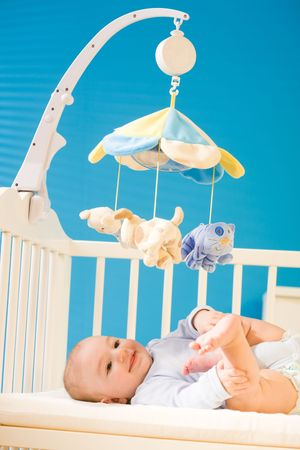 4 months old happy baby boy lying on crib playing with his cute littel feet, smiling. Toys are officially property released. Stock Photo - 3199998