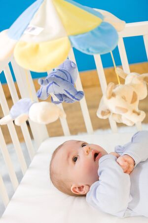 hanging toy: Four months old little boy palying in baby bed. Toys are officially property released.