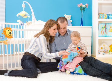 Happy family (father, mother and 1 year old baby girl) playing together at home, sitting on floor in children's room, smiling. Toys are officially property released. Stock Photo - 3200003