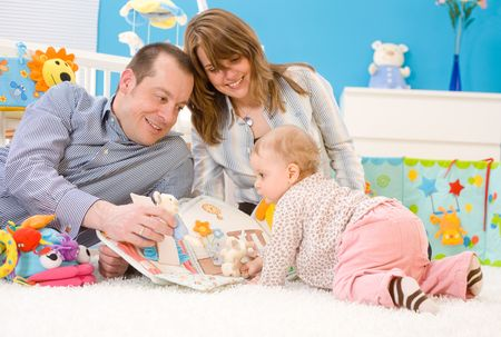 Happy family playing together: mother, father and 1 year old baby girl sitting on floor at children's room, smiling. Toys are officially property released. Stock Photo - 3200001