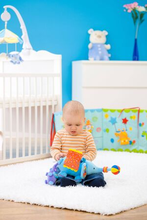 Little baby boy (1 year old) sitting on floor at children's room and playing with toys. Toys are officially property released. Stock Photo - 3199995