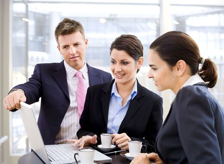 Young business people working over a laptop computer and drinking coffee. Stock Photo - 3199992