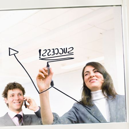 Businesswoman drawing linegraph on office window to illustrate growth and success. Happy businessman calling on phone, smiling. Stock Photo - 3199987