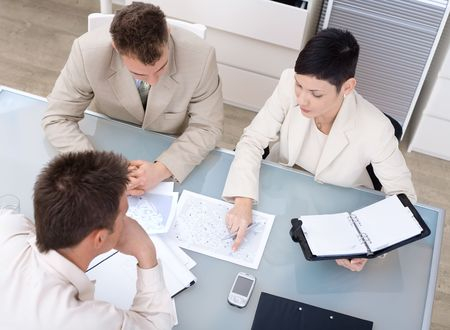 training consultant: Businessteam of three working together, sitting around a desk, high angle view.