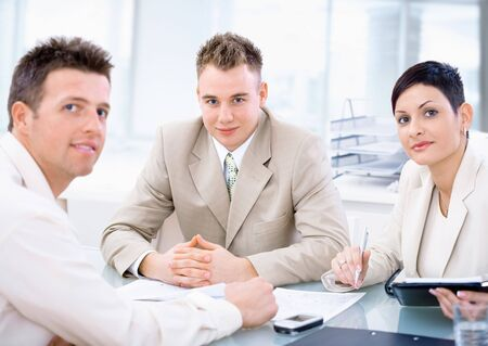 Businessteam of three working together, sitting around a desk, looking at camera. Stock Photo - 3199993