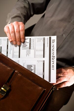 Business man opening elegant brown leather briefcase to take out printed business report. Stock Photo - 3200002