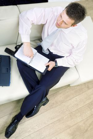 Busy businessman sitting on sofa at office or at home and writing to notebook, high angle view. Stock Photo - 3199999