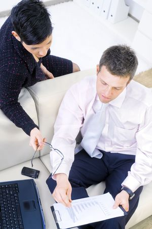 Consultants looking at business chart, sitting on sofa at office, high-angle view. Stock Photo - 3200000