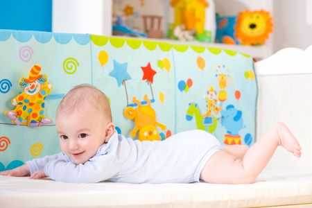 cuddly baby: Happy baby boy (4 months old) lying on front in baby bed and smiling. Toys are officially property released.