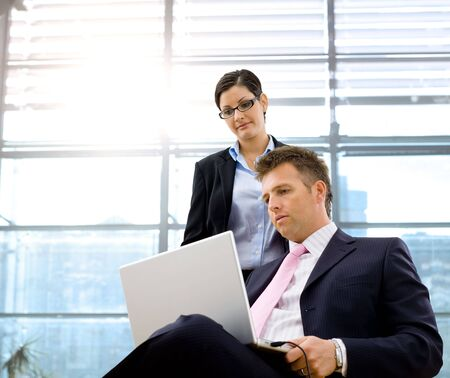 color consultant: Serious mature businessman sitting and using laptop computer, businesswoman standing and working together.