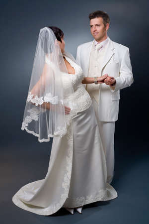 wedding photography: Bride and Groom posing in wedding dress at studio, looking at each other, smiling.
