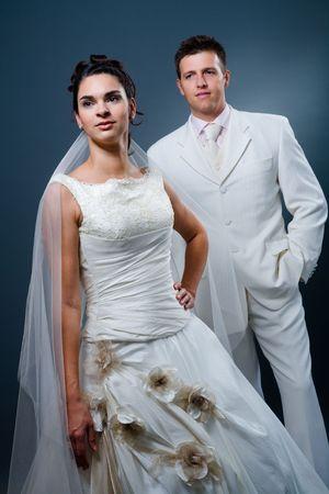 wedlock: Happy bride and groom posing together in studio, wearing wedding dress, smiling.