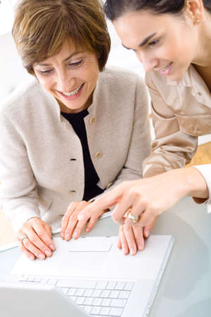 Senior businesswoman and young assistant working  at desk in office, smiling. Stock Photo - 3200011