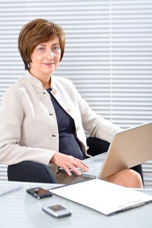 secretary phone: Senior businesswoman working in office, using laptop, smiling.