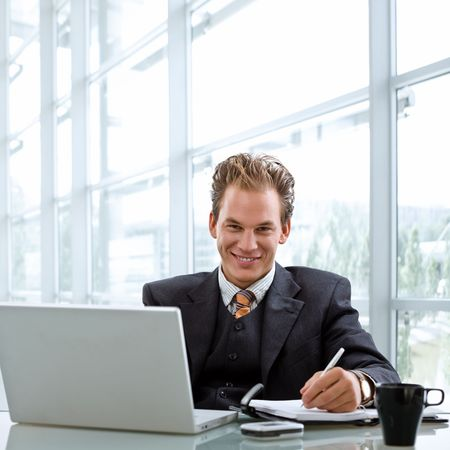 Happy smiling businessman working on laptop computer at desk. photo
