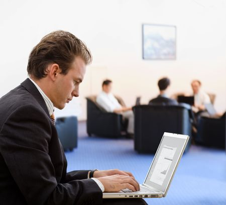Businessman working on laptop computer at office lobby. Stock Photo - 3774933