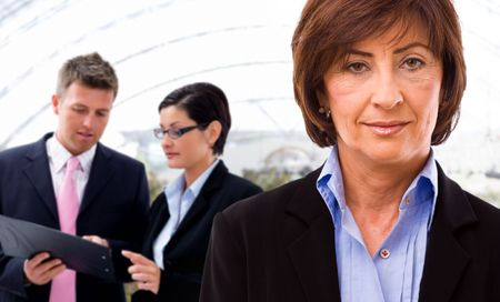 Senior businesswoman with working business team in background.  Stock Photo