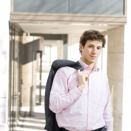 officetower: Happy young businessman standing in front of office building, effortless, shirt with open collar with jacket on shoulder, smiling. Stock Photo