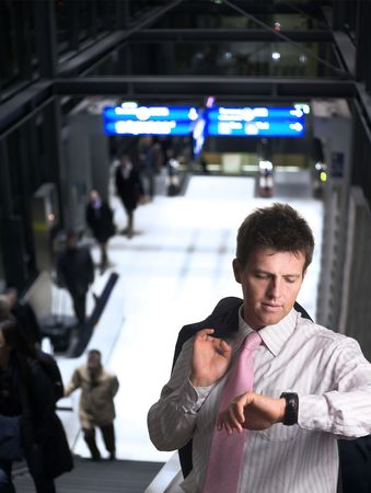 Businessman is standing on the escalator on a railwaystation or airport. He is checking the time on on his watch. photo