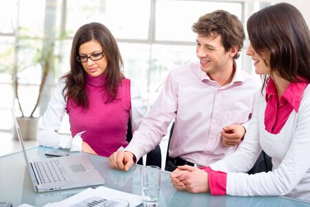 Happy young business people having meeting at office, looking at laptop computer, smiling. Stock Photo - 3785458