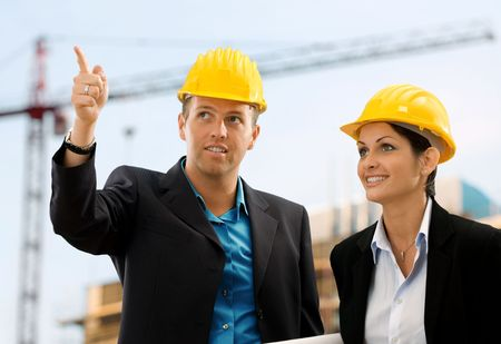 contruction: Happy architects wearing protective helmet working and talking on contruction site. Stock Photo