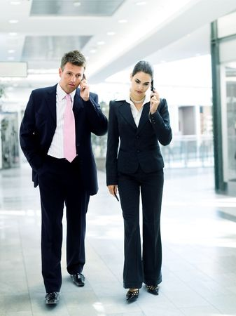 Busy business people walking and calling on mobile.  Stock Photo - 3785408