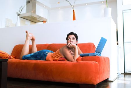 outwork: Young women is resting on the couch and surfing the internet on her laptop computer.  Maybe she is dreaming of an online friend. Stock Photo