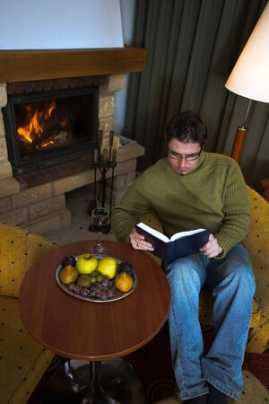 Man is sitting in the armchair at home in front of the fireplace. He is reading the book. photo