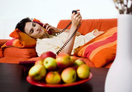 Young women is resting on the couch and receiving a phone call. photo