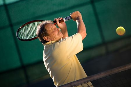 Active senior man in his 70s playing tennis. photo