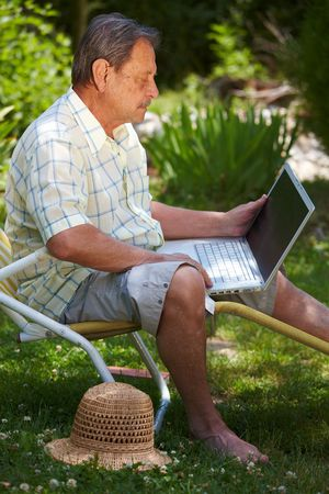 telework: Healthy senior man is his elderly 70s sitting outdoor in garden at home and using laptop computer to browse internet.